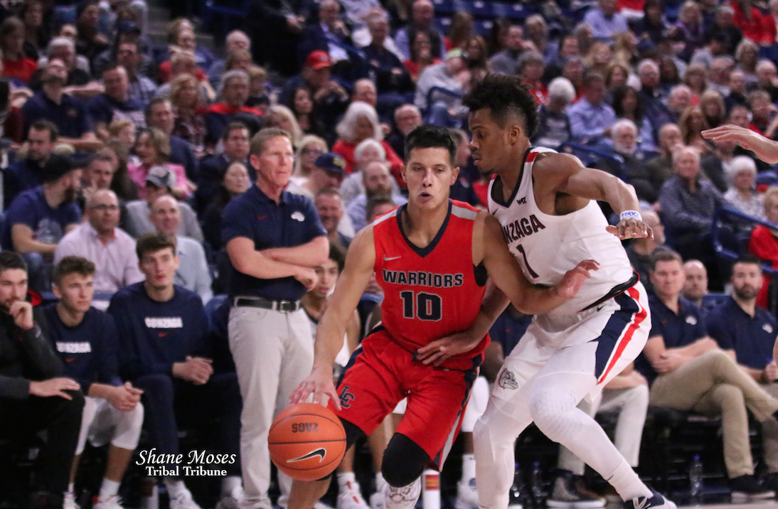 Tribal member Dedrick Pakootas (#10 red) of Lewis and Clark State College drives to the hoop against Gonzaga's Admon Gilder, Nov. 8, in a exhibition matchup at the Kennel. Gonzaga coach Mark Few watches in the background.