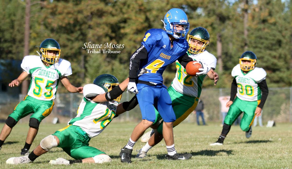 Adonis Seymour (#18 white) of Inchelium attempts to make a tackle against a Wellpinit runner on Friday (Oct. 11) afternoon