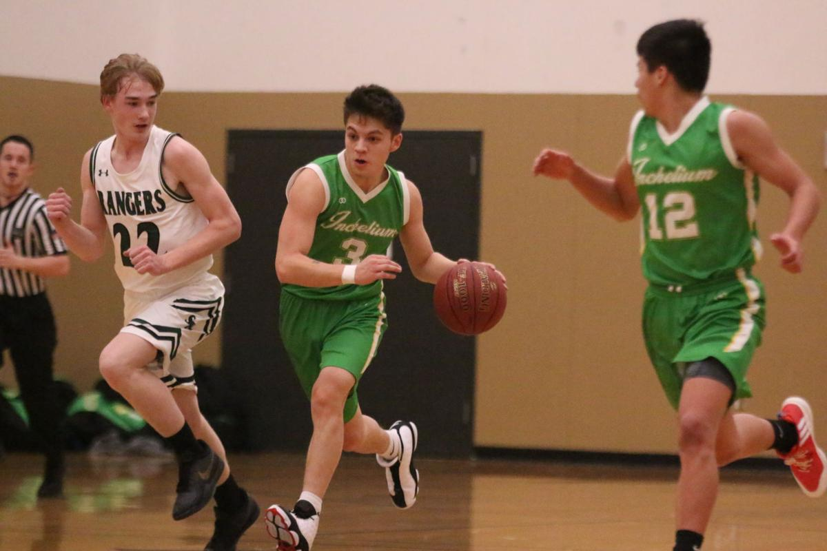 Colville tribal member Jake Flett (#3 green) of Inchelium dribbles the ball up court against Cusick on Wednesday evening at the District 7 1B boys basketball tournament at Deer Park High School