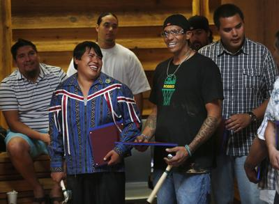 Colville Tribal member Cole Stanger, left, at the graduation ceremony of the Tulalip Trade School where Stanger and his classmates built micro-houses for homeless.
