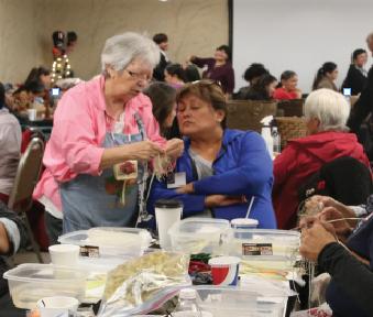 Tribal member Tillie Gorr shows and instructs fellow tribal member Charlene Cohen on how to weave a cornhusk basket.