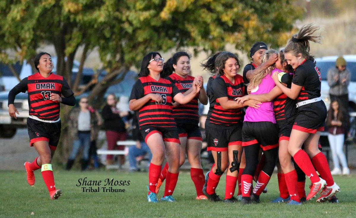 The Omak girls soccer team runs and swarms Kacie Vejraska, (pink) as she would go on to score the winning goal against Chelan on Thursday (Oct. 10) afternoon in a shootout. Omak won the shootout 4-3