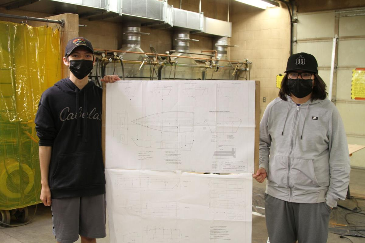 Colville tribal members Elijah and Aidan Palmanteer stand with their plans for a 16-foot skiff they have worked on through the Grand Coulee Dam School District's Summer School Career Technical Education Program
