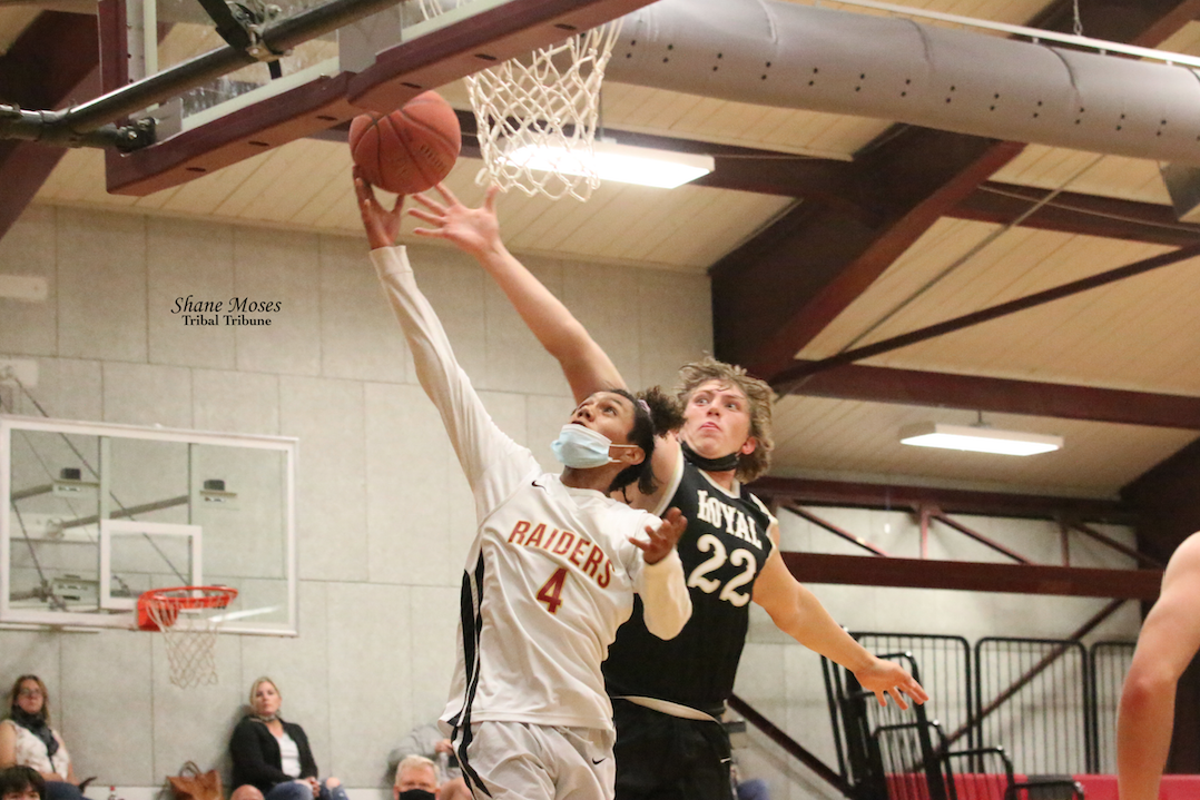Colville tribal member Brandon Pino (#4 white) of Lake Roosevelt attacks the glass going up for a lay in against Royal (June 14) on the play