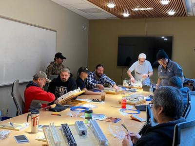 Instructor Guy Sanford, standing center, leads a class through hands on fiber optic training at the Lucy F. Covington Government Center.