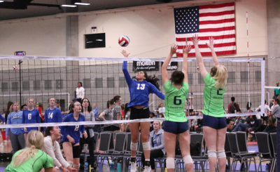 Mia Smith (#13 blue) of the Splash 18's goes up and drops a shot past the outstretched arms of a Seattle based team on Saturday afternoon at the Pacific Northwest Qualifier at the Spokane Convention Center.