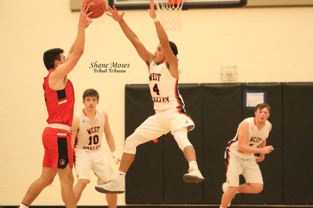 West Valley's Dakari Pakootas (#4 white) jumps up in the air to try and deflect a pass against Clarkston on Wednesday (Jan. 29) evening.