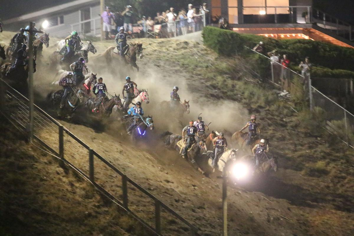 Jockeys and their horses make their way down the 220-foot hill on Thursday night in the first of four races for this year's Suicide Race.