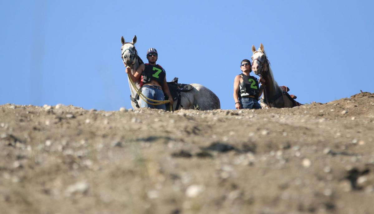 LEFT TO RIGHT: Colville tribal members Oliver Pakootas and his horse Onyx and Jordan Pakootas and his horse Woosta stand at the top of the hill as both jockeys prepare for the second elimination race on Sunday afternoon (August 5).