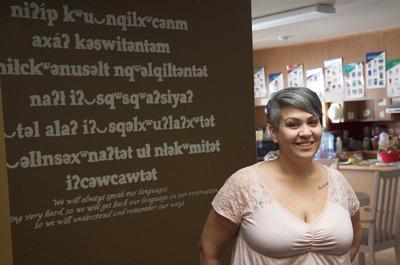 Inchelium Language and Culture Association Executive Director Stevey Seymour stands under a skylight in the Inchelium Language House, where nselxcin, or Okanogan, language is featured on a wall behind her on Feb. 9.