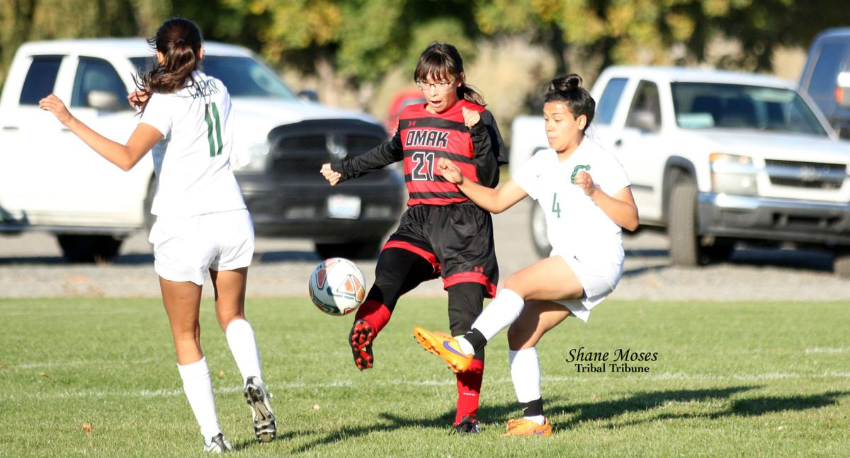 Tribal member Taylor Palmanteer (#21 black) of Omak tries to deflect the ball away from Chelan's Wendy Mendez (#4 white) on Thursday (Oct. 10) afternoon