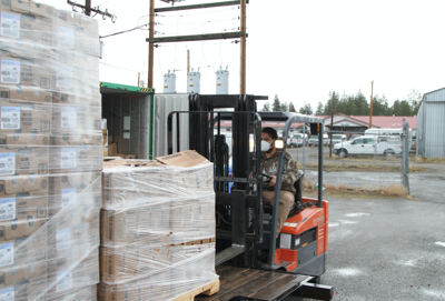 Colville Tribal member Calem Louie, who works at the Colville Tribal Food Distribution Program, unloads a trailer load of turkeys donated to the Colville Tribes from Pacific Aquaculture.