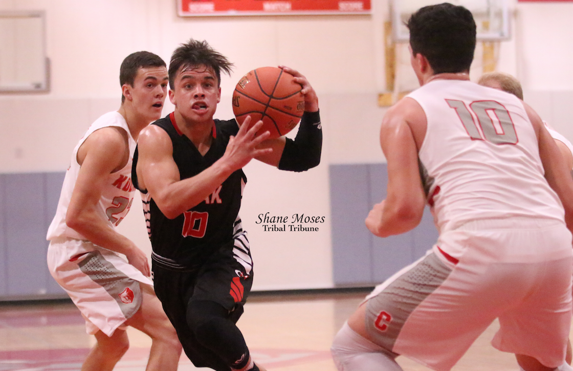 Tribal member Jaren Boyd (#10 black) of Omak drives to the hoop against Cascade earlier in the season.