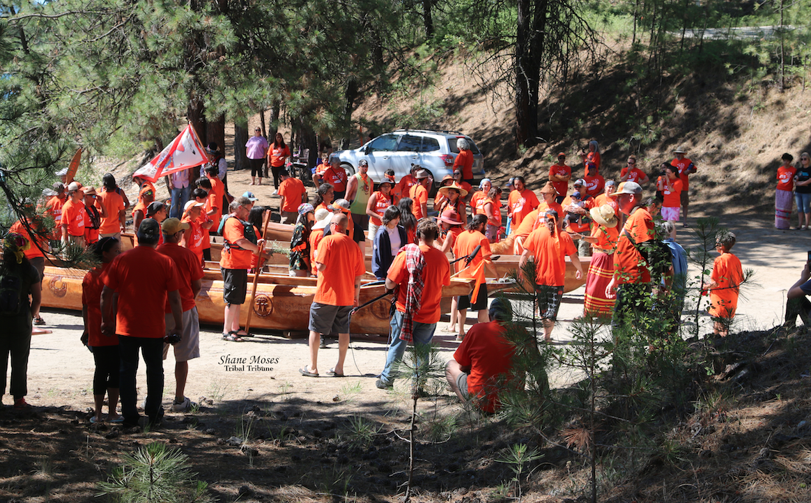 Paddlers gather for a prayer following the landing of canoes at Kettle Falls, June 20