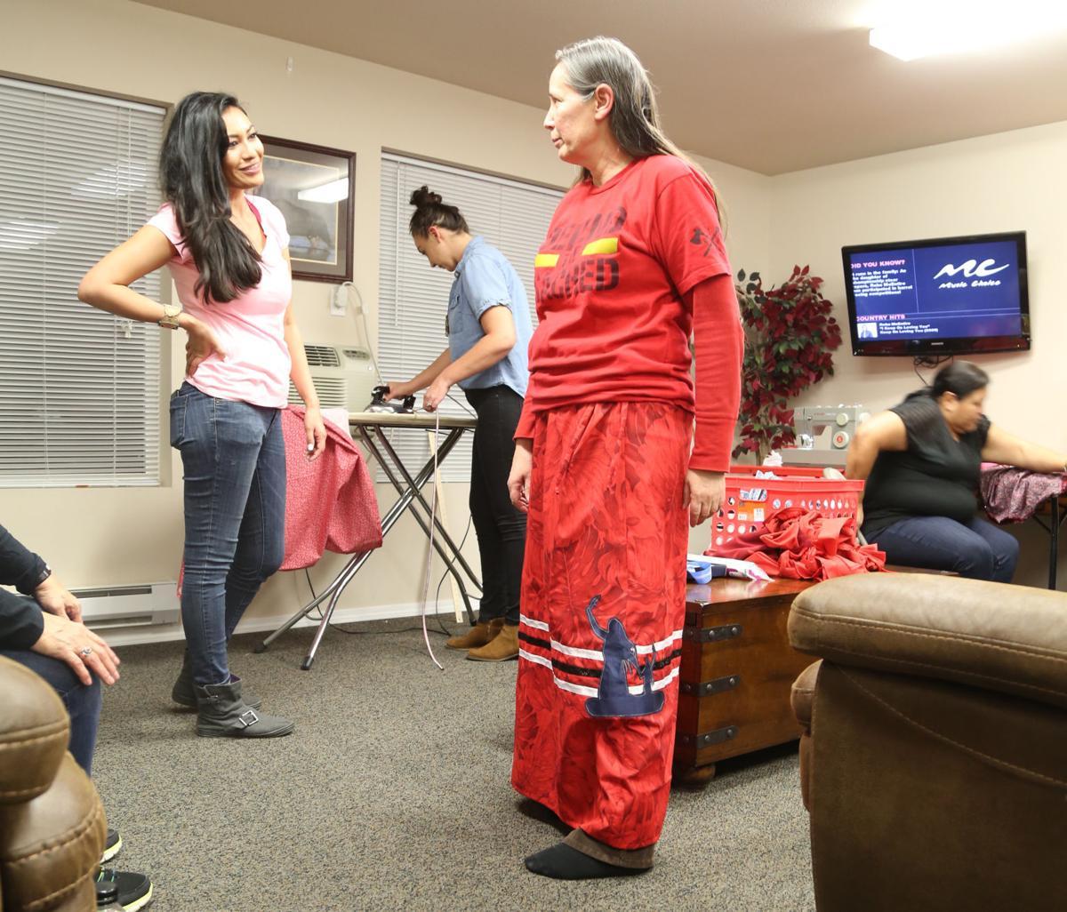 Colville tribal member Shawnee Bearcub, left, talks with Spokane tribal member Melodi Wynne after Wynne finished her skirt tonight in Airway Heights.