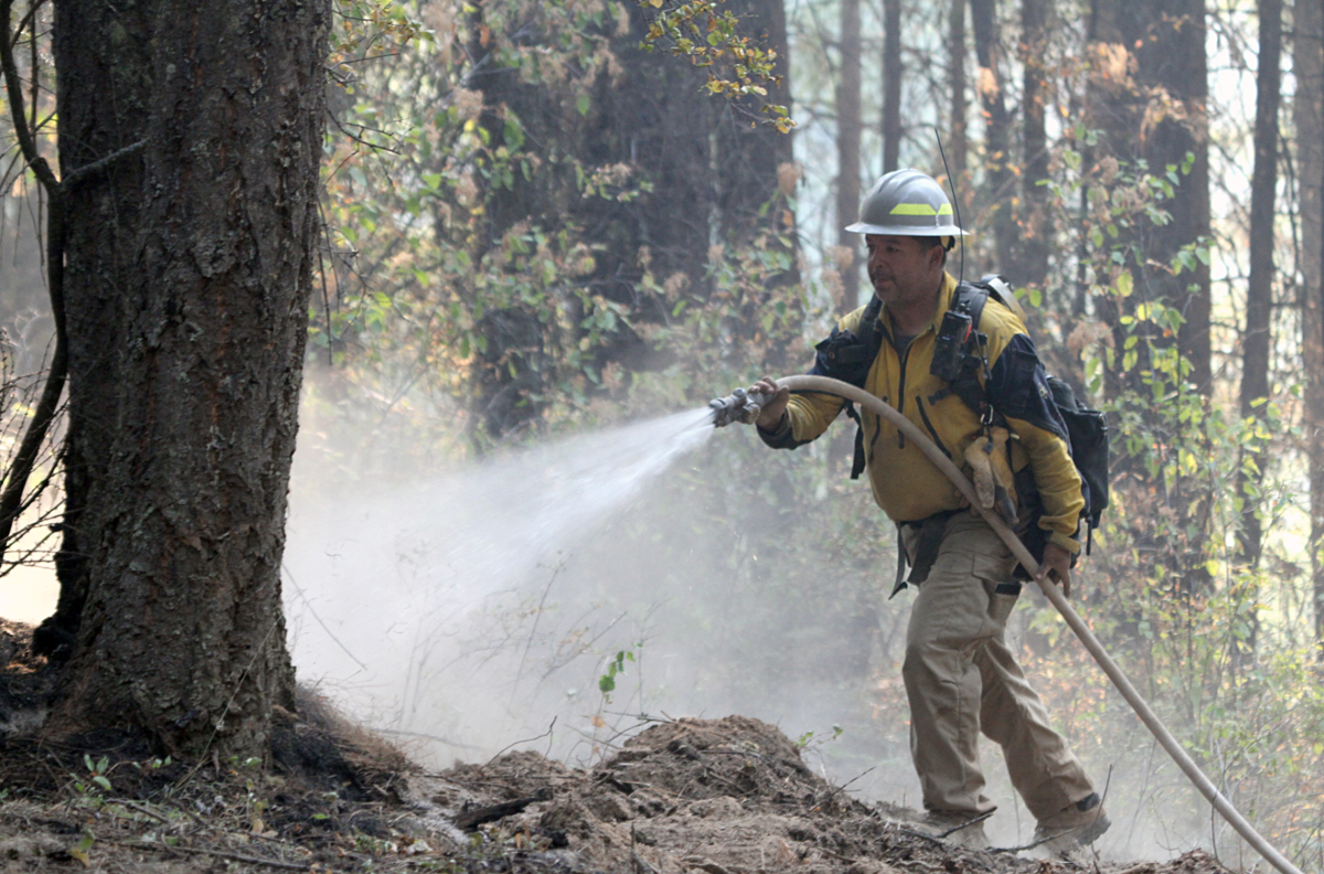Colville Tribal member Victor Ensminger, a task force leader, douses flames with a hose on the Fry Fire near Inchelium, Sept. 13.