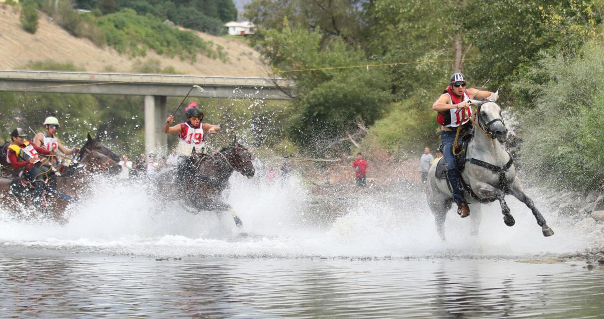 Oliver Pakootas (#10) and Onyx (grey horse) lead the way out of the Okanogan River on Sunday afternoon