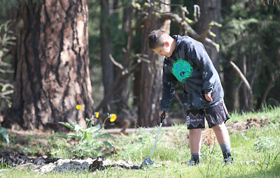 An Inchelium school student picks up garbage during Earth Day.