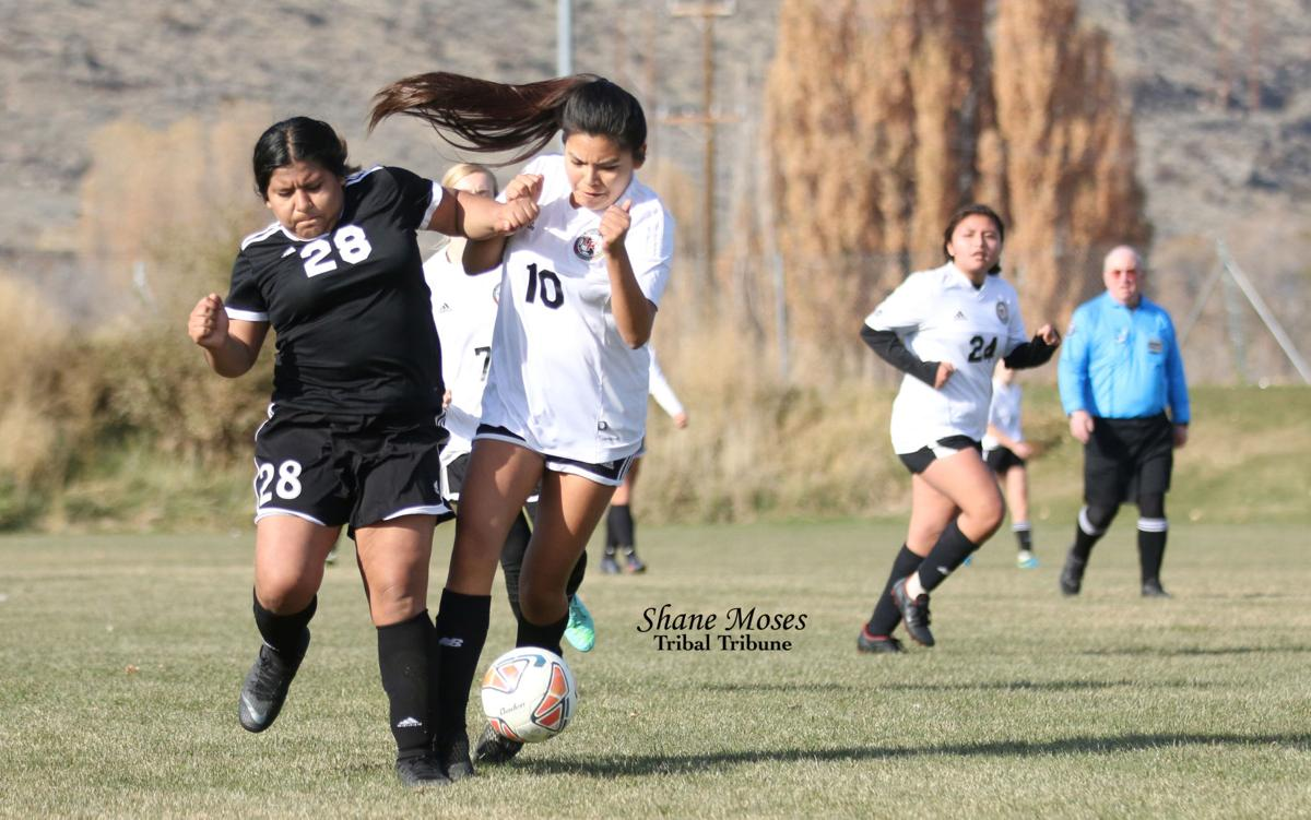 Colville tribal member Glad Eyes Williams (#10 white) of Lake Roosevelt battles with Bridgeport's Aracely Valdovinos for the ball on Saturday (Nov. 2) afternoon