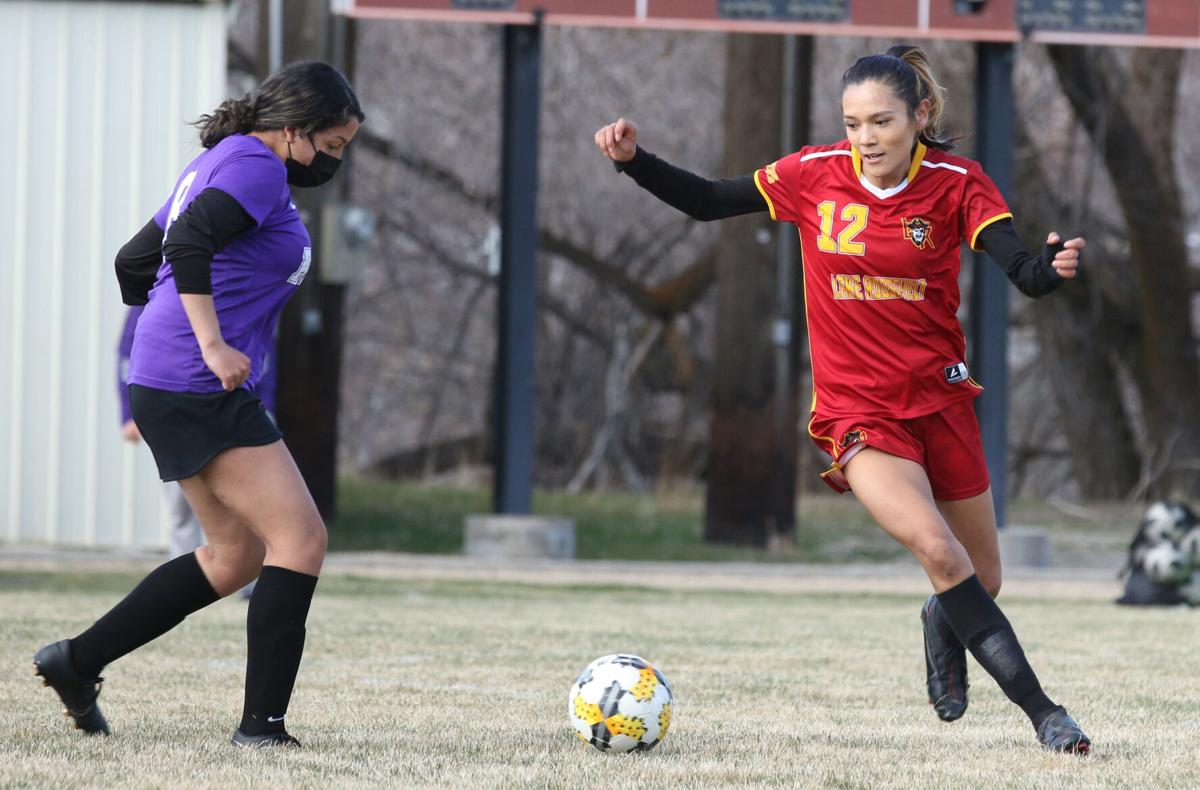 Colville tribal member Kyona Edmo (#12 red) of Lake Roosevelt dribbles away from Pateros defenders on March 25. Lake Roosevelt won 6-3.