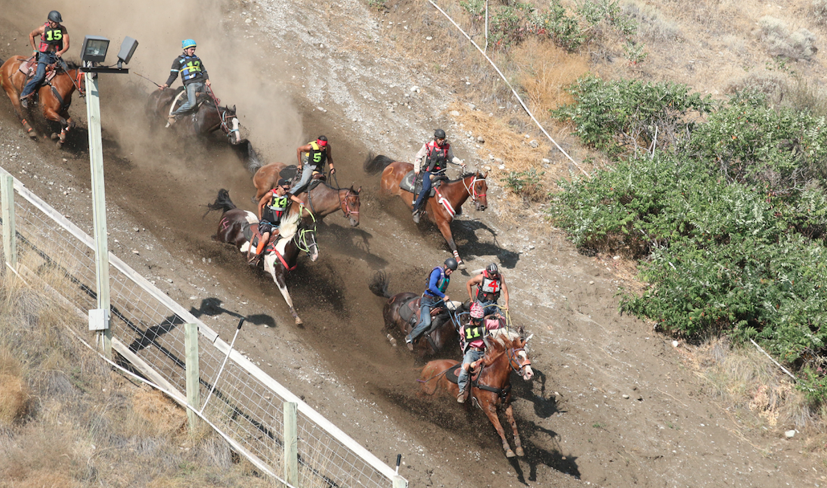 Jockeys and their horses charge down the 220-foot hill en route to the Okanogan River during the second elimination race on Sunday afternoon