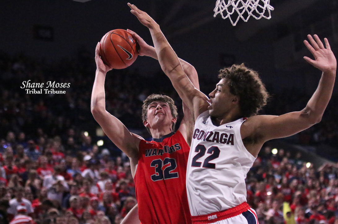 Trystan Bradley (#32 red) of Lewis and Clark State College goes up for a lay in against Gonzaga's Anton Watson (#22 white) on Friday (Nov. 1) evening in a exhibition matchup at the Kennel