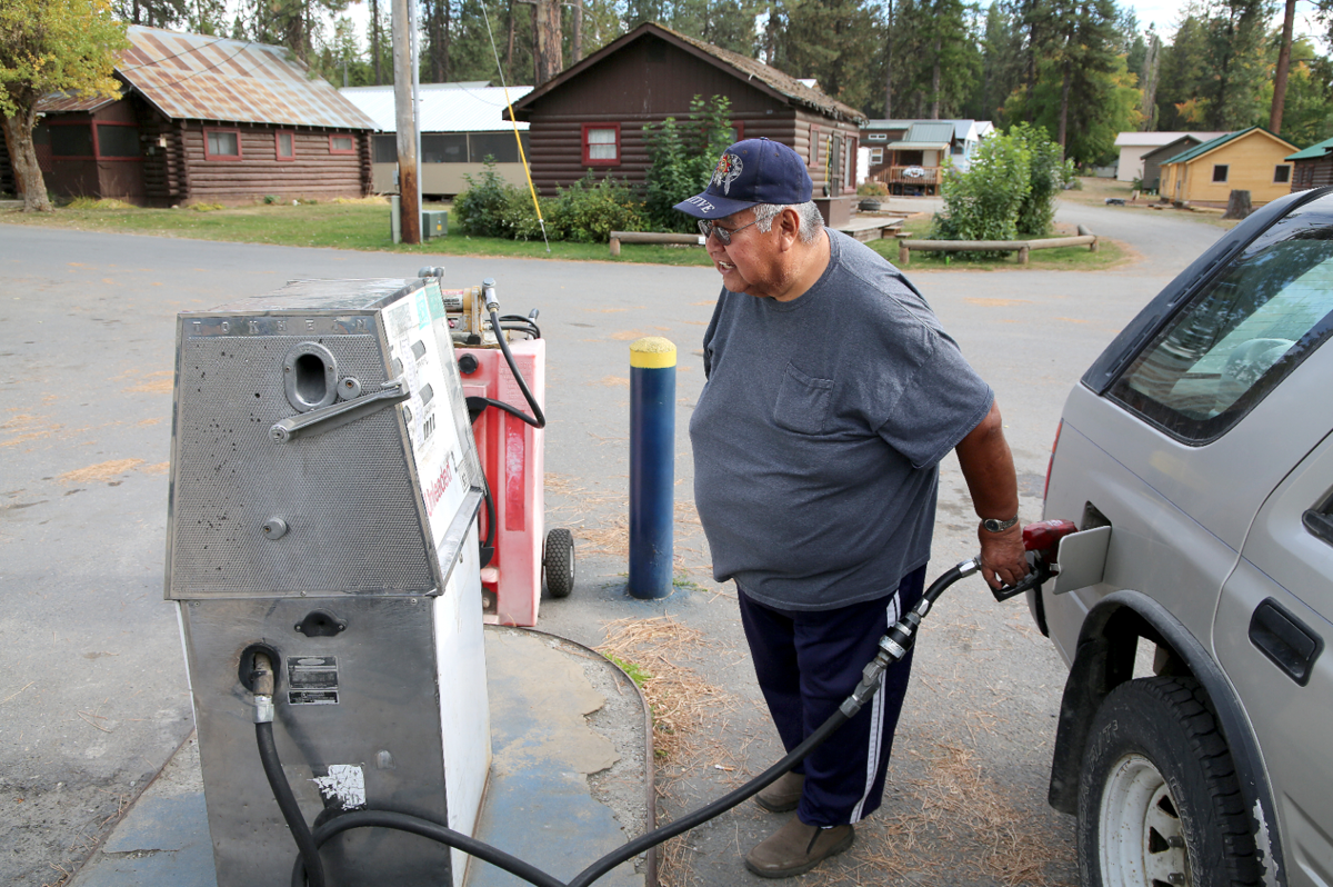 Clem Nicholas gasses up at Rainbow Beach Resort, where prices are $3.11 for tribal members on Friday.