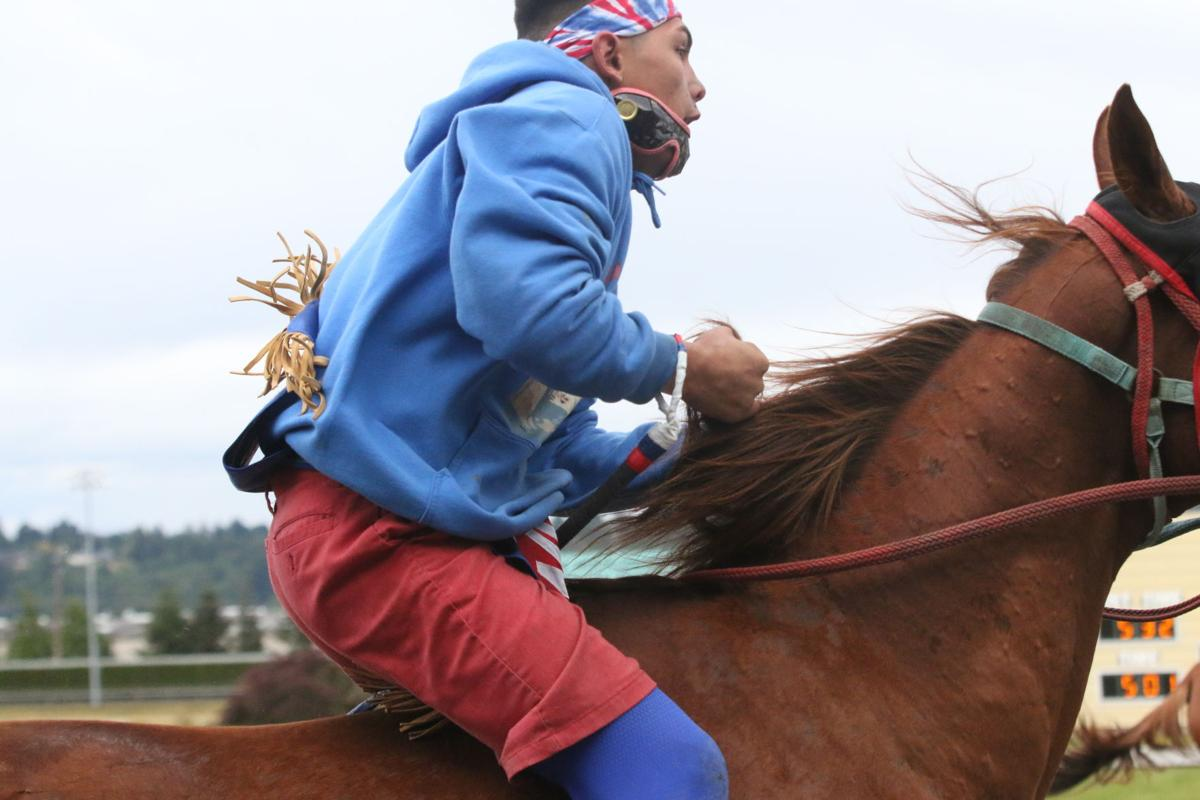 Colville tribal member Matthew Pakootas Jr., jockey for Northwest Express rides in front of the grand stand on his way to the next exchange during the second consolation race on Sunday afternoon at the third annual Muckleshoot Gold Cup at Emerald Downs racetrack in Auburn