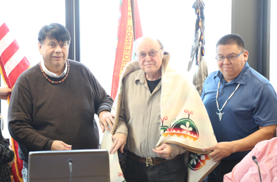 Colville Business Council chair Rodney Cawston, left, stands with William Layman and CBC member Darnell Sam, chair of the CBC Culture Committee, during session, Dec. 5. CBC gifted Layman with a Pendleton blanket following Layman's donation of research material to the tribe.