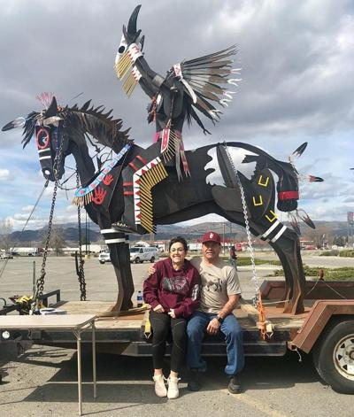 Virgil 'Smoker' Marchand sits with his daughter, Tara, in front of a sculpture made in honor of his son, the late Duran Marchand, Sr.