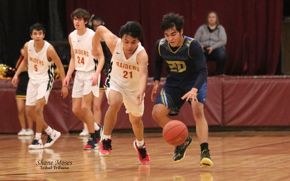 Tribal member Adam George (#21 white) of Lake Roosevelt attempts to steal the ball away from Oroville's Sergio Ocampo on Friday (Feb. 14) night in the semifinals of the CWA 2B boys' district tournament. Lake Roosevelt won 69-52.