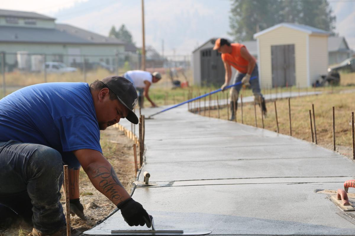 Colville member Shane Palmer, working with Jesse Palmer Construction, smooth freshly poured concrete in creating a bike path at Nespelem Head Start in August.