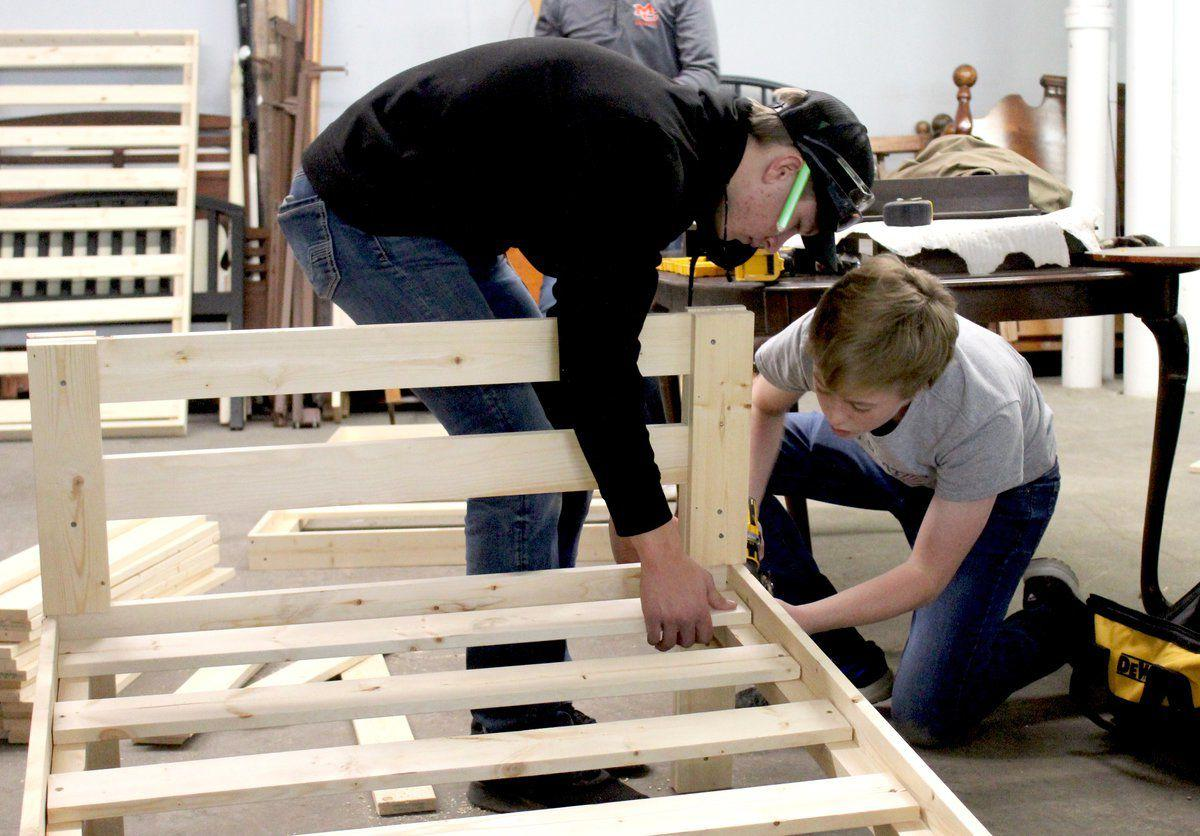 Local students build beds for families in need