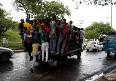 HANGING ON: Commuters ride on a cargo truck used for public transport in Valencia, Venezuela, on July 11. –Photo: REUTERS