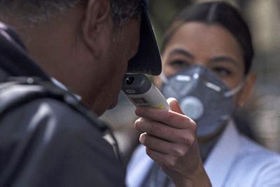 A nurse checks a man's temperature