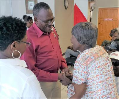 Housing Minister Edmund Dillon greets oldest Techier resident Sylvia Br...