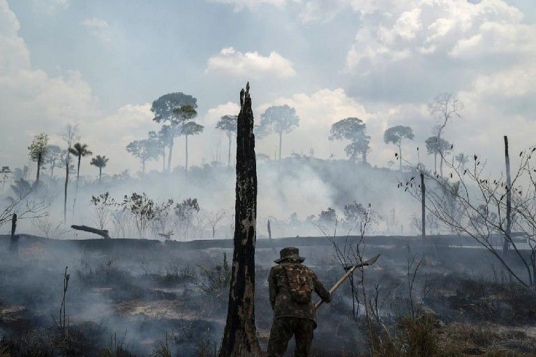 A Brazilian soldier puts out fires at the Nova Fronteira