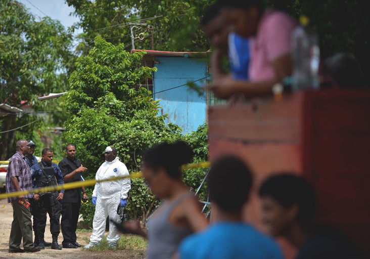 Police officers at the crime scene where sixteen-year-old Noah Simmons was murdered at the old train line, Union Park East, Marabella, yesterday morning. -Photo: DEXTER PHILIP