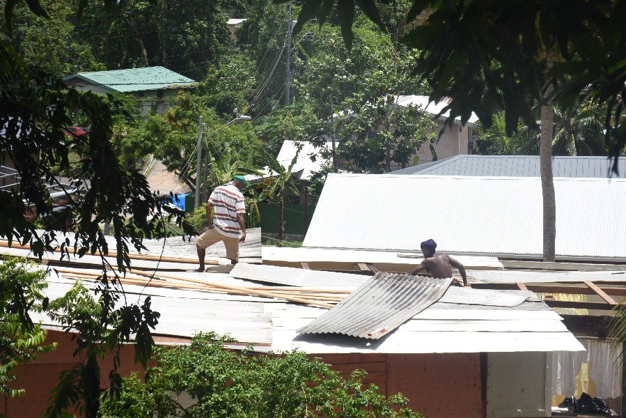 Workmen repair the roof of a house at Poptie Trace