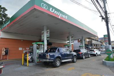 Motorists line up at the pumps yesterday at the Unipet Service Station