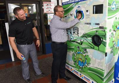 Massy Stores CEO Derek Winford, right, demonstrates how the Kansmacker's reverse vending machine works at Massy Stores, West Mall, Westmoorings, last week. At left is Joseph Rahael. —Photo: Curtis Chase