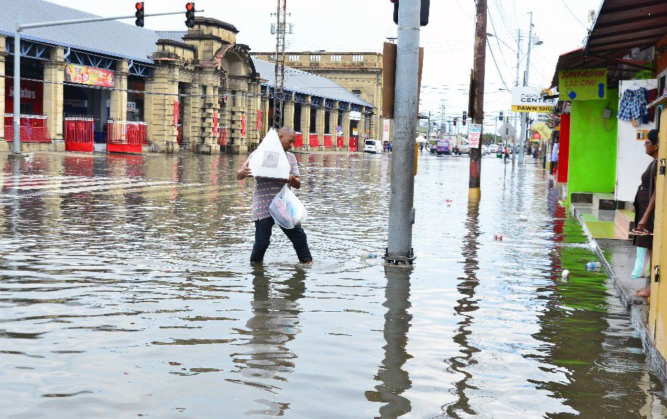 pedestrian walks through floodwaters on South Quay