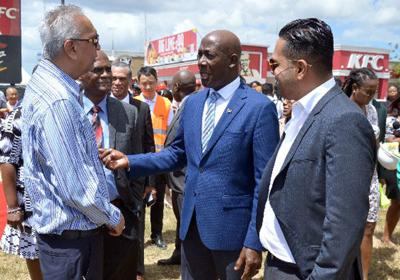 Prime Minister Dr Keith Rowley speaks with contractors Junior and Shaun Sammy