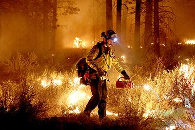 A firefighter sets a backfire