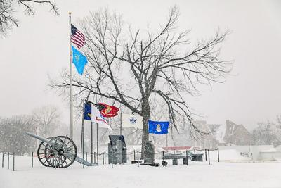 Snow falling over veteran memorial