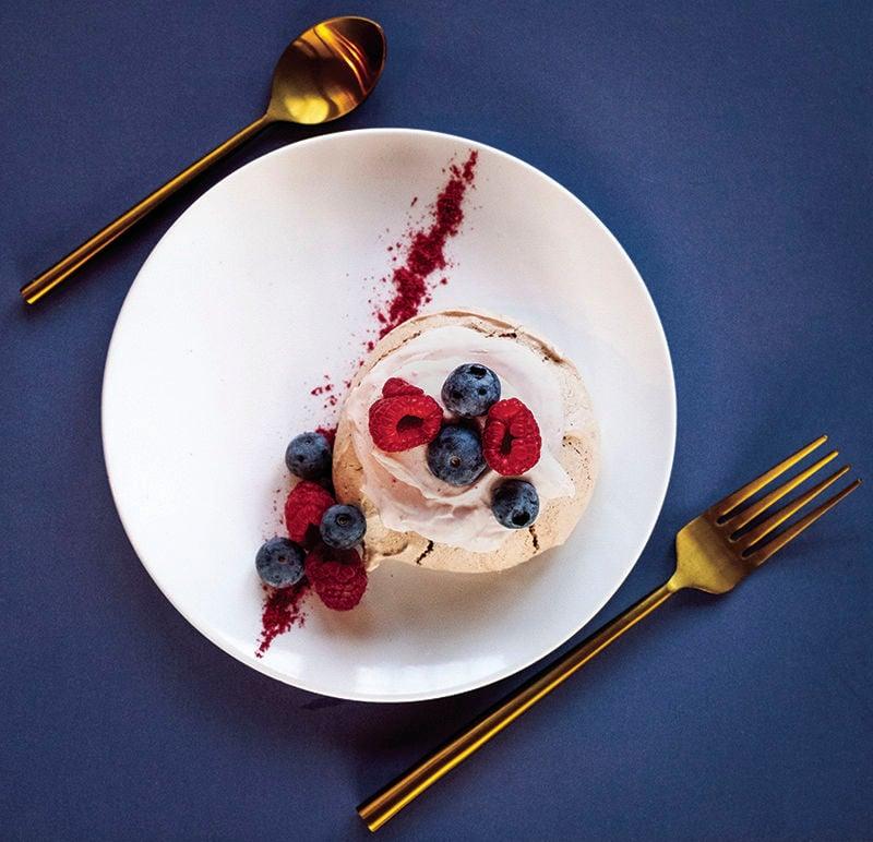 Chocolate pavlova with berries and raspberry dust