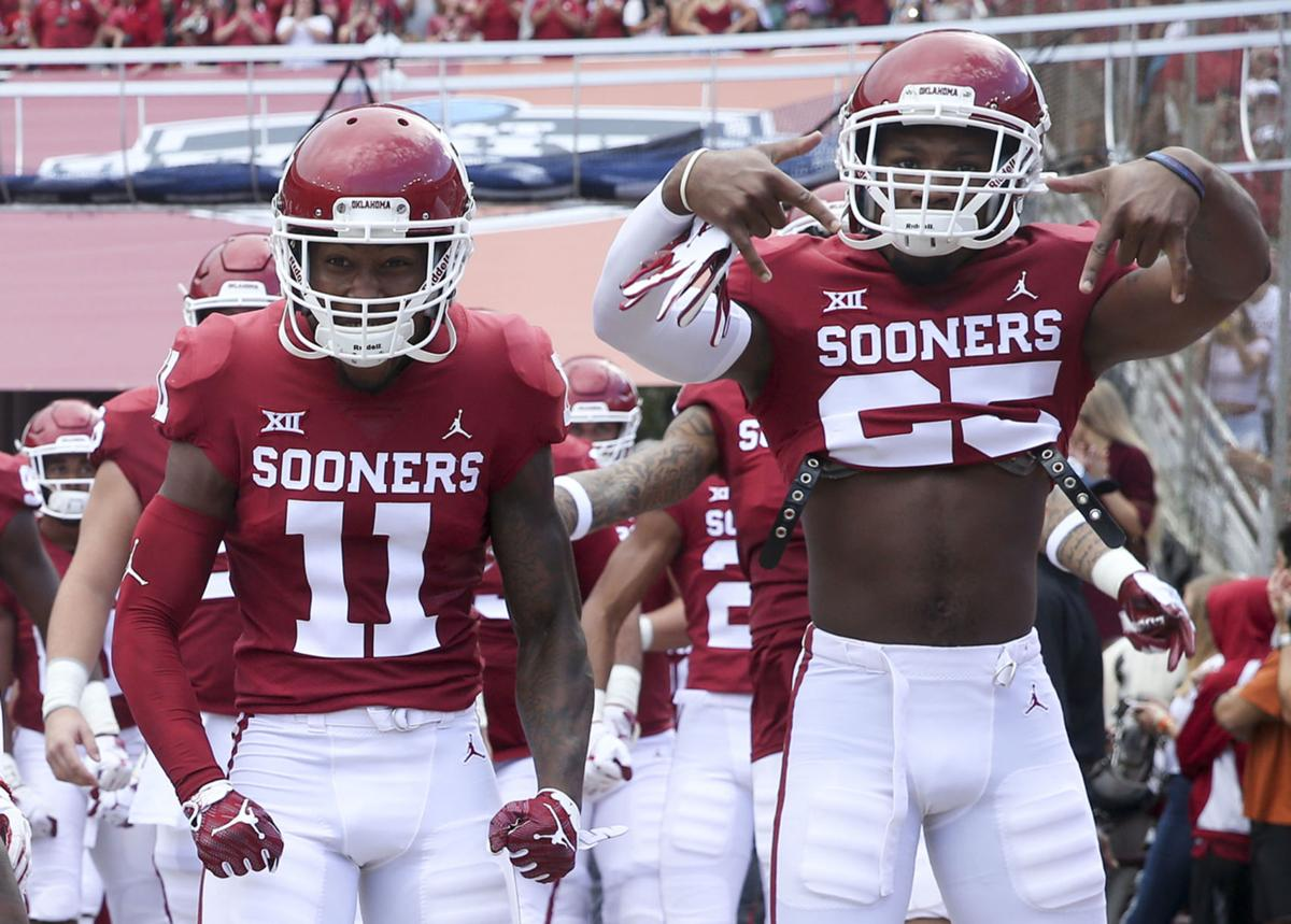 """5a99d122cc71 Oklahoma Sooners defensive back Justin Broiles (25) signals """"Horns down"""" as  he and cornerback Parnell Motley (11) take the field before the Red River  ..."""