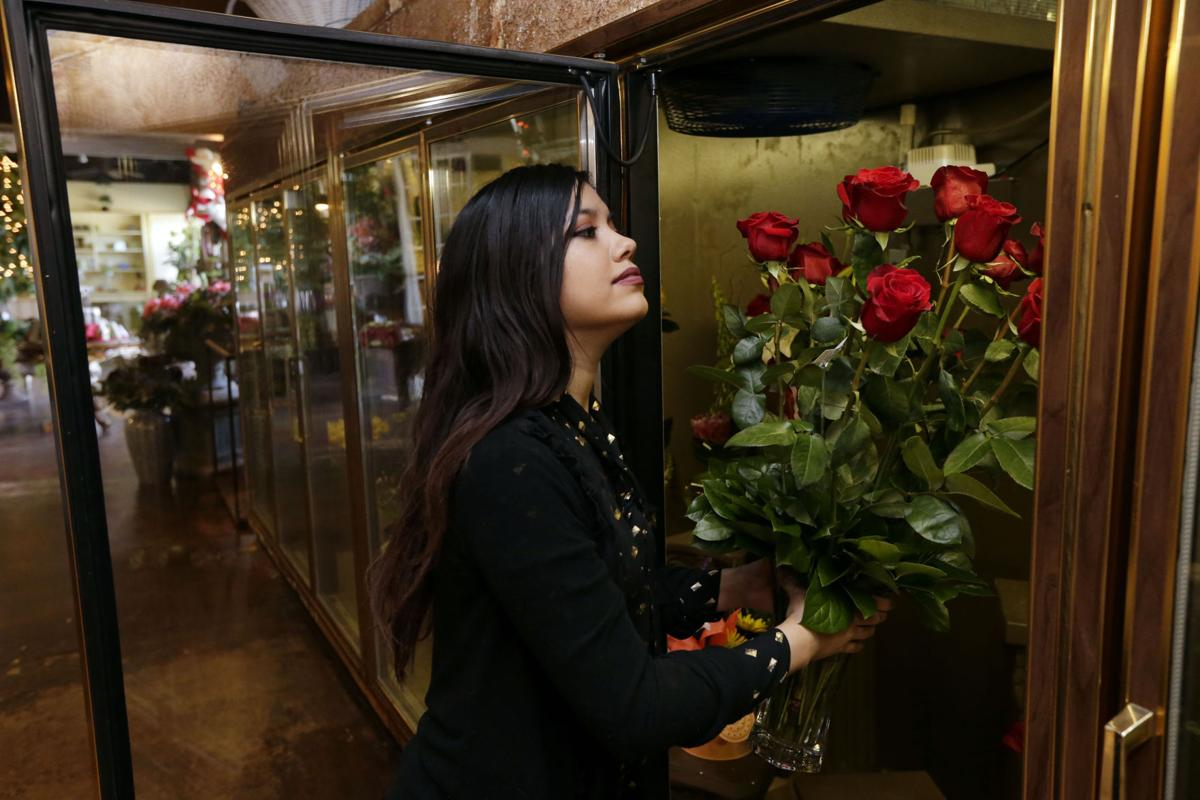 Marcella Carreno, floral sales representative at Burnett's Flowers and Gifts, takes out roses from the coolant refrigerator on Friday.