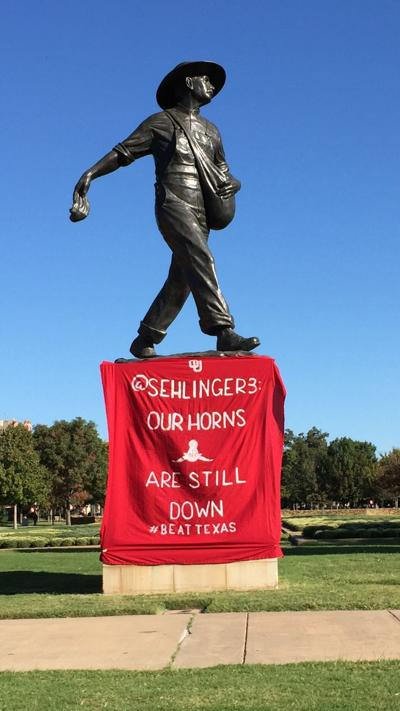 """OU football: Fans present a """"horns down"""" message to Texas quarterback Sam Ehlinger on the iconic Sooner Sower statue"""