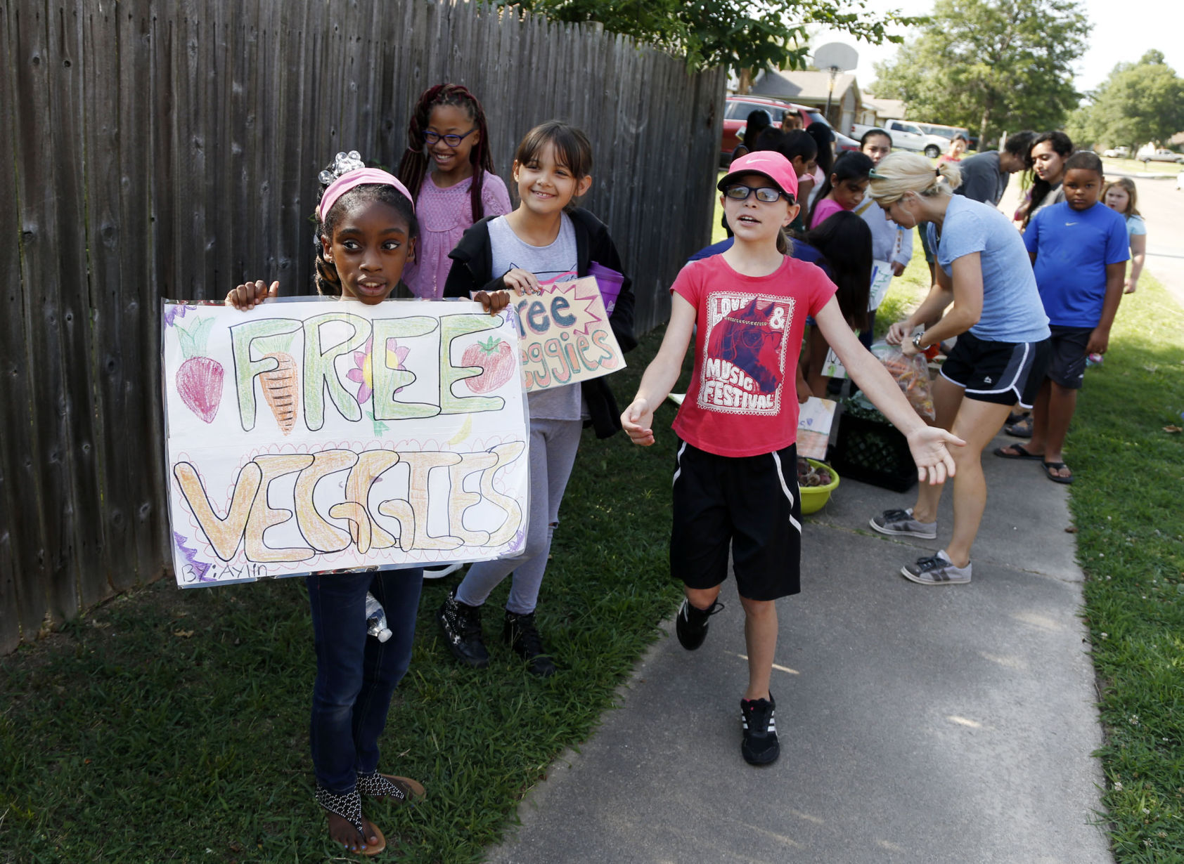 Kids hand out free veggies they grew